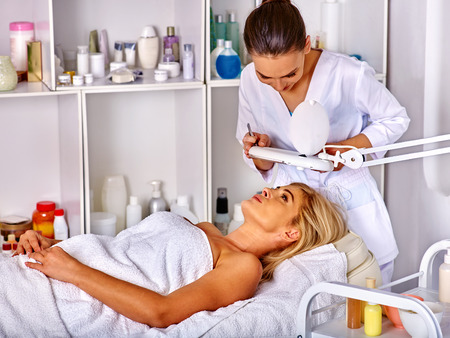 Woman middle-aged in spa salon with young beautician. Tweezing eyebrow by beautician in spa salon.