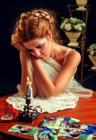 ragazza innamorata: Donna triste soffre di matrimonio fallito, ha guardato le immagini e tenendo la sua testa. Sposa abito da sposa interni e in background. Sono masterizzazione di candela sul tavolo.