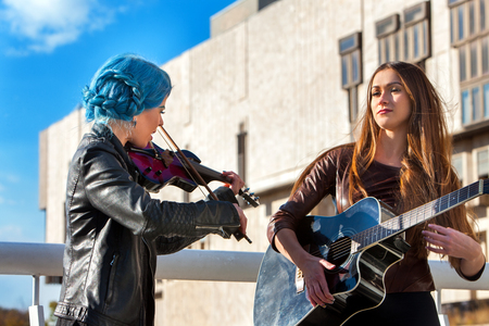 Music street performers two girls violinist with blue hair playing aganist sky with clouds outdoor. Autumn mood. Violinist girls playing in city outdoor.