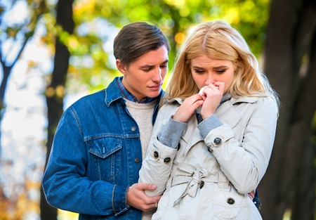 lovers quarrel: Betrayal and forgiveness couple. Girl is crying with handkerchief on outdoor.