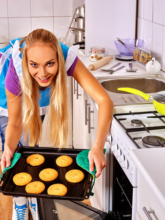 bap: Young blond smiling woman bake cookies. Cooking on home kitchen.