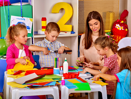 Los niños del grupo con el maestro están haciendo algo fuera de papel de colores sobre la mesa en la escuela primaria. lección, los niños de artesanía en la escuela primaria.