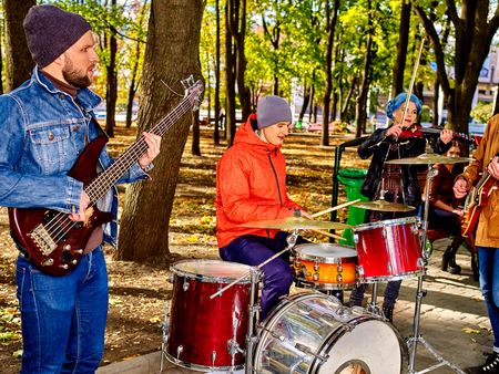 citypark: Group of music street performers with girl violinist on autumn citypark outdoor. Stock Photo