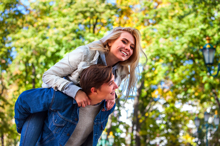 Young couple hugging and flirting in fall park and looking away. Fall is season it brings many changes. Stock Photo