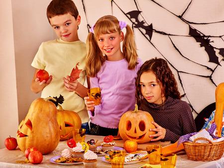 children party: Children on Halloween party making carved pumpkin. Children look forward to Halloween.