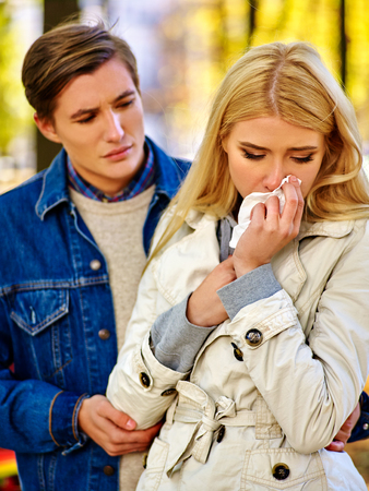 persuade: Girl is crying and telling guy about an unwanted pregnancy. Man tries to persuade her not to have an abortion. Girl is crying with handkerchief on fall park outdoor.