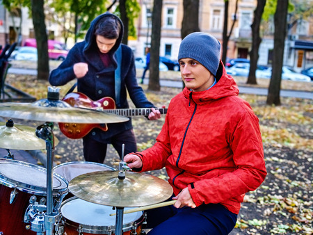 street musician: Music street male buskers playing percussions on autumn outdoor. Real mans music in autumn park