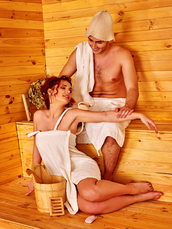 bathers: Couple in love into sauna hat have relax at sauna. Steam and high heat make bathers perspire.