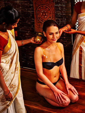 Woman having Ayurvedic spa treatment. Pouring massage oil. Two masseuses Hindu doing massage girl sitting on his lap.