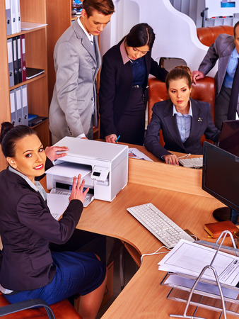 out of business: Happy group business people in office. Woman is printing out. Business as usual.