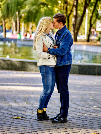 Young couple kissing in autumn park . Loving couple kissing in sun in autumn park. He just called her to say I love you.
