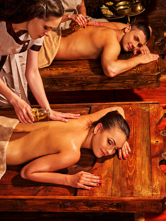 spa woman: Couple in love having oil Ayurveda spa treatment on wooden bed. India exotic relaxing treatment .