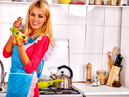 woman alone: Happy woman eating salad at kitchen. Salad for slim figure. Woman teaches cooking salad in kitchen alone.