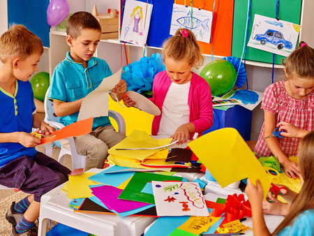 Children are making something out of colored paper on table in primary school. Children craft lesson in primary school. Development children craft at class in school. Children make overall project.