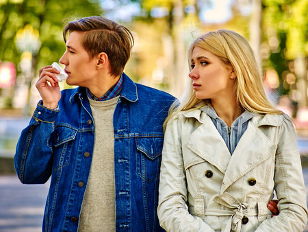 cold season: Man with cold rhinitis on autumn outdoor. Fall flu season. Girl looks with compassion on suffering of loved one. During autumn season lot of people suffer from allergies and disease.