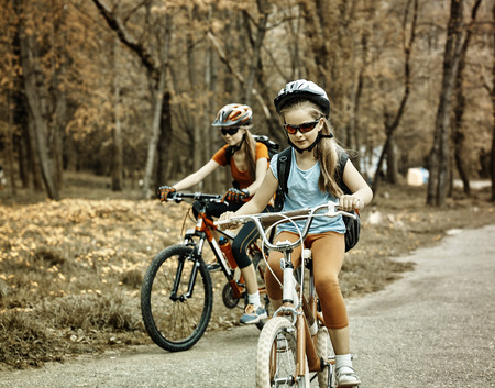 Bikes bicyclist girl. Toned sepia image. Girls wearing bicycle helmet with rucksack ciclyng bicycle. Child in foreground teenager on background.