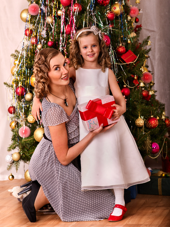 Child with mother receiving near Christmas tree. Mother and daughter greeted Christmas.