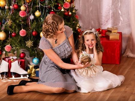 niños vistiendose: Niño con la madre que recibe cerca del árbol de Navidad. La mama da hija Muñeca de la Navidad.