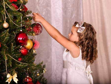 Child decorate on Christmas tree. Little girl getting dressed Christmas ball. Stock Photo