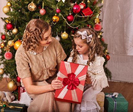 niños vistiendose: Niño con la madre que recibe cerca del árbol de Navidad. La mama da caja de regalo de la hija con el arco rojo. Foto de archivo