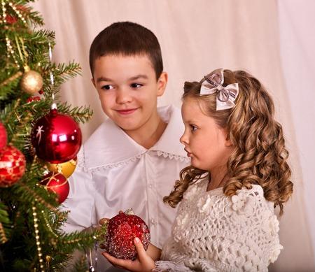 niños vistiendose: Los niños que reciben los regalos bajo el árbol de Navidad. Hermano y hermana juntos. Foto de archivo