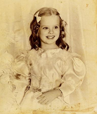 niños vistiendose: Retrato retro de la muchacha del niño decorar el árbol de navidad. blanco y negro retro sepia en el papel viejo. Foto de archivo