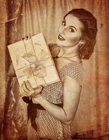 Retro portrait of woman holding gift box. Black and white retro on old paper. Stock Photo
