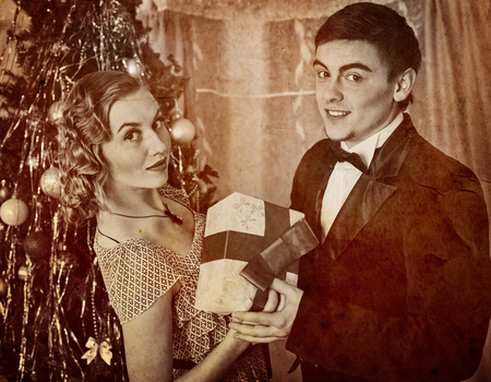 Retro vintage portrait of couple on party near Christmas tree. Black and white retro on old paper. Stock Photo