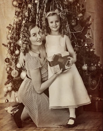 niños vistiendose: Family portrait of child with mother receiving gift near Christmas tree. Black and white retro on yellow old paper. Foto de archivo