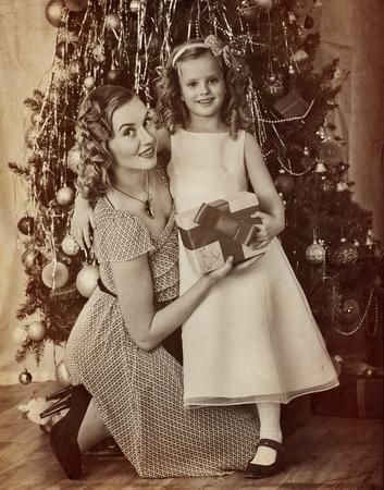 niños vistiendose: Retrato de la familia del niño con la madre que recibe el regalo cerca del árbol de Navidad. retro blanco y negro en el papel viejo de color amarillo.
