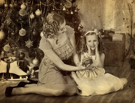 niños vistiendose: Child with mother receiving gift near Christmas tree. Mother keeps doll toy for daughter. Black and white retro family portrait.