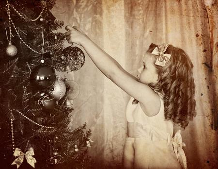 niños vistiendose: Retro viejo retrato de la muchacha del niño decorar el árbol de navidad. foto retro blanco y negro.