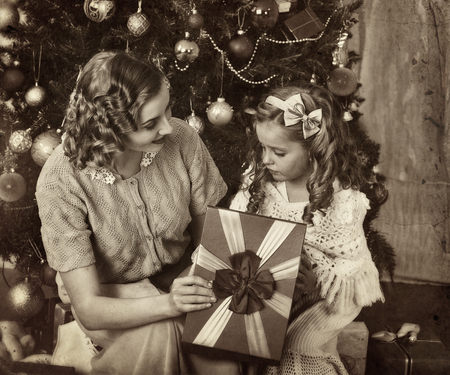 niños vistiendose: Niño con la madre que recibe cerca del árbol de Navidad. retro blanco y negro.