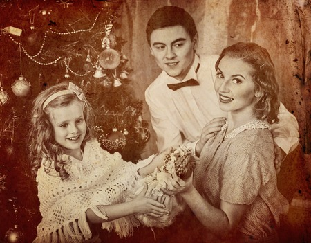 niños vistiendose: Portrait of family with children dressing Christmas tree. Father hugs his wife and daughter. Black and white retro.