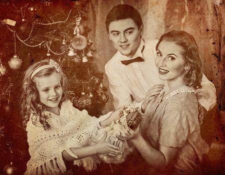 niños vistiendose: Retrato de familia con los niños que viste el árbol de Navidad. Padre abraza a su esposa e hija. retro blanco y negro.