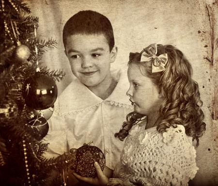 niños negros: Retrato retro de los niños hermano y hermana decoración del árbol de Navidad. foto retro blanco y negro sobre papel amarillo.
