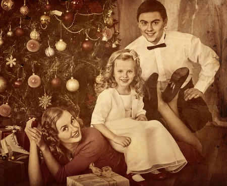 family with children pose under christmas tree black and white retro family portrait stock - Black Family Christmas Pictures