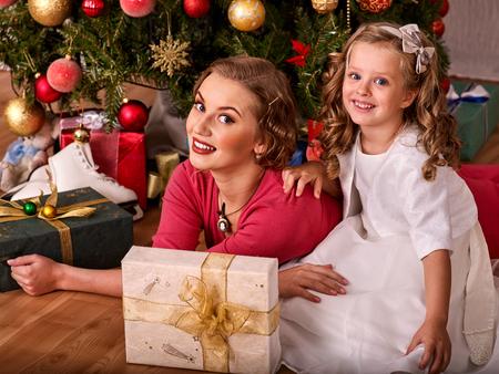 niños vistiendose: Retrato retro de la muchacha del niño con la madre que recibe cerca del árbol de Navidad. estilo retro vieja foto. Una gran cantidad de regalo en cuadro.
