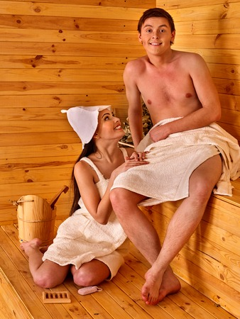 Group people in hat relaxing at sauna. Two persons. woman tenderly looking at her boyfriend.