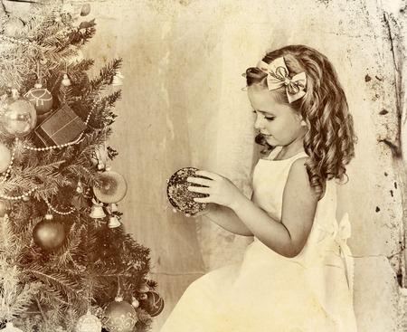 niños vistiendose: Niño decorar el árbol de navidad. vieja foto en papel amarillo. niño solo en casa. Foto de archivo