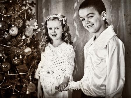niños vistiendose: en blanco y negro niños y fotos bajo el árbol de Navidad. estilo retro de Navidad. Viejo cuadro. Hermano y hermana se reúnen Navidad.