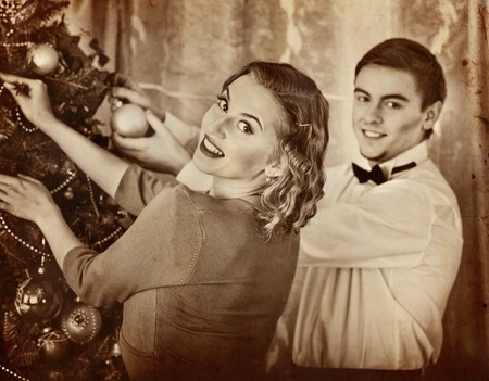 Couple on party decoration Christmas tree. Black and white retro.Old photo on yellow paper. Stock Photo
