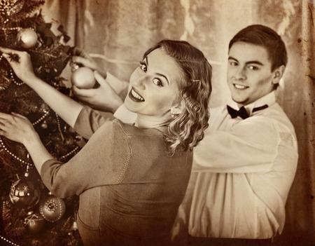 postcard: Pareja en la decoración del partido del árbol de navidad. foto blanco y negro retro.Old en papel amarillo. Foto de archivo