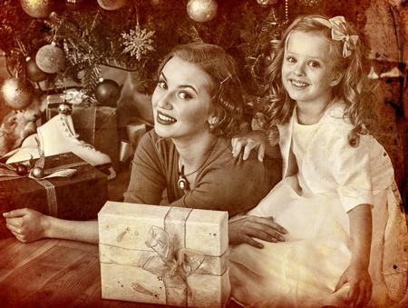 niños vistiendose: niña con la madre que recibe cerca del árbol de Navidad. vieja foto en papel amarillo. estilo retro vieja foto. Regalo en rectángulo plano.