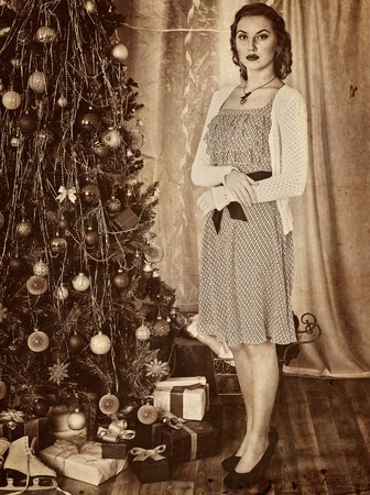 photo pictures: Portrait of woman receiving gifts under Christmas tree. Old photo on yellow paper. Retro style pictures.