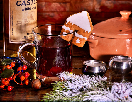 Hot drink on spruce branches with snow. Hot punch with red wine with cookie in form of house on brick wall. Stock Photo