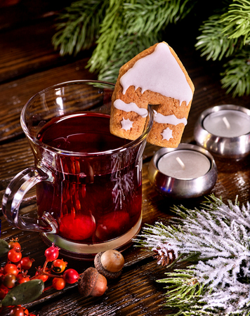 punch spice: Still life of winter hot drink and spruce branch. Warming mulled wine with cookie in form of house. Top view. Stock Photo