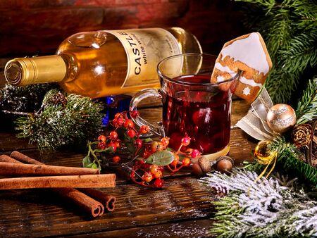 ginger cookies: Taza de cristal de grog caliente que yacía junto a la botella de vino tinto. bebida de invierno de Navidad. galleta de jengibre en forma de casa en la taza. Bola de Navidad y chamota.