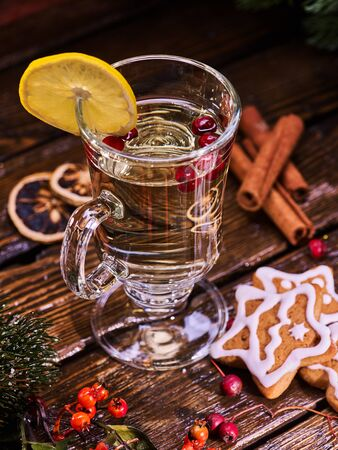 mag: Christmas glass latte mug and Christmas multicolored cookies on plate with fir branches. Mag decoration lemon slice on wooden table in restaurant and cinnamon sticks.