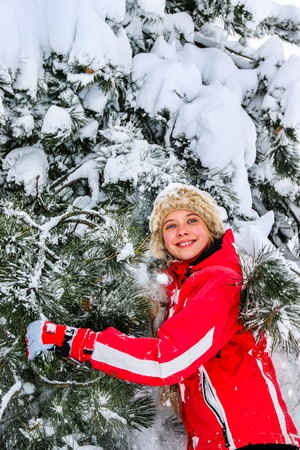 Teenager girl wearing winter clothes lying in snow .Teenager shakes off snow from branches of trees. Winter cold forest.